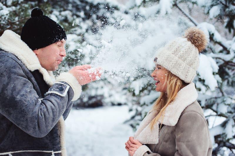 retrato del invierno de los pares felices nieve que juegan, el soplar y pasando el buen día al aire libre en bosque nevoso fotos de archivo libres de regalías