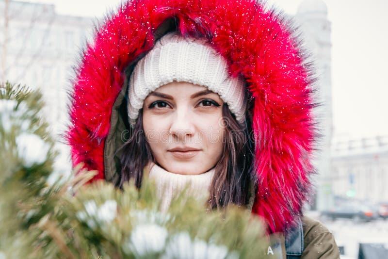 Retrato del invierno de una muchacha delante de un árbol de navidad verde fotos de archivo libres de regalías