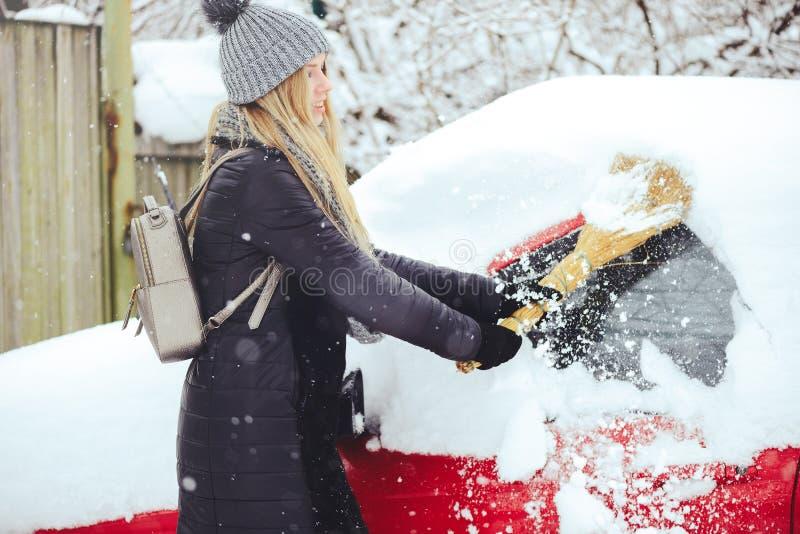 Retrato del invierno de una nieve de la limpieza de la mujer joven de un coche La belleza Girl modelo rubio ríe y limpia alegre l imágenes de archivo libres de regalías