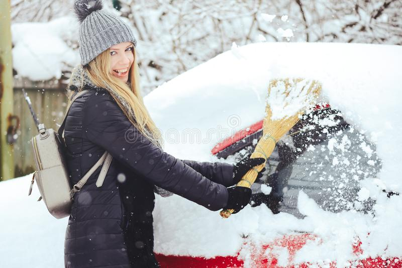 Retrato del invierno de una nieve de la limpieza de la mujer joven de un coche La belleza Girl modelo rubio ríe y limpia alegre l foto de archivo libre de regalías