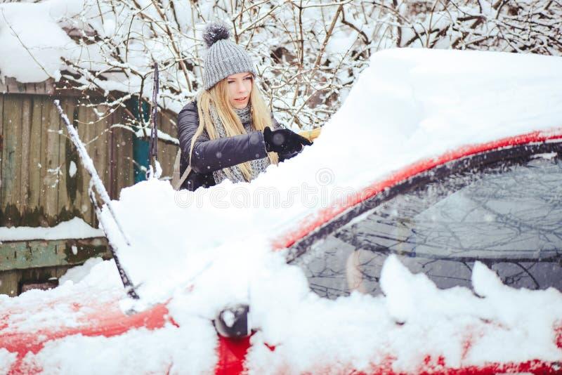 Retrato del invierno de una nieve de la limpieza de la mujer joven de un coche La belleza Girl modelo rubio ríe y limpia alegre l imagen de archivo