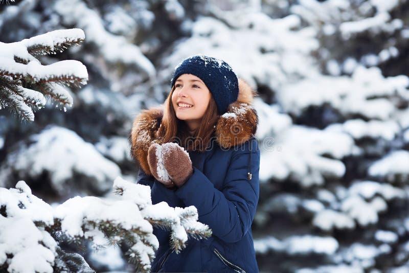 Retrato del invierno: Muchacha bonita joven vestida en ropa de lana caliente, bufanda y cabeza cubierta planteando el exterior imagenes de archivo