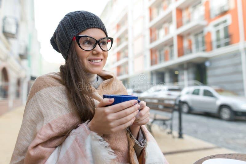 Retrato del invierno del otoño de la mujer sonriente joven en sombrero, con la taza de bebida caliente Fondo de la calle de la ci imagen de archivo