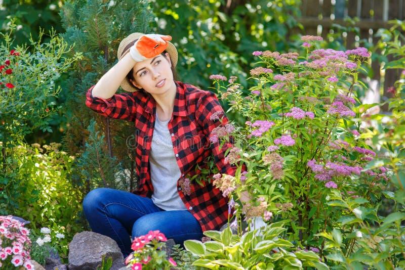 Retrato del jardinero cansado de la mujer joven foto de archivo