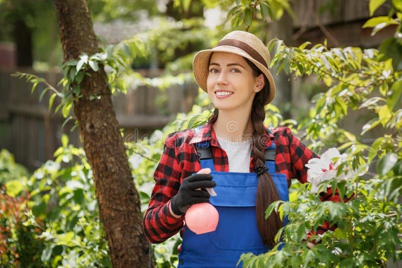 Retrato del jardinero de sexo femenino en ropa de trabajo con la botella del espray fotos de archivo