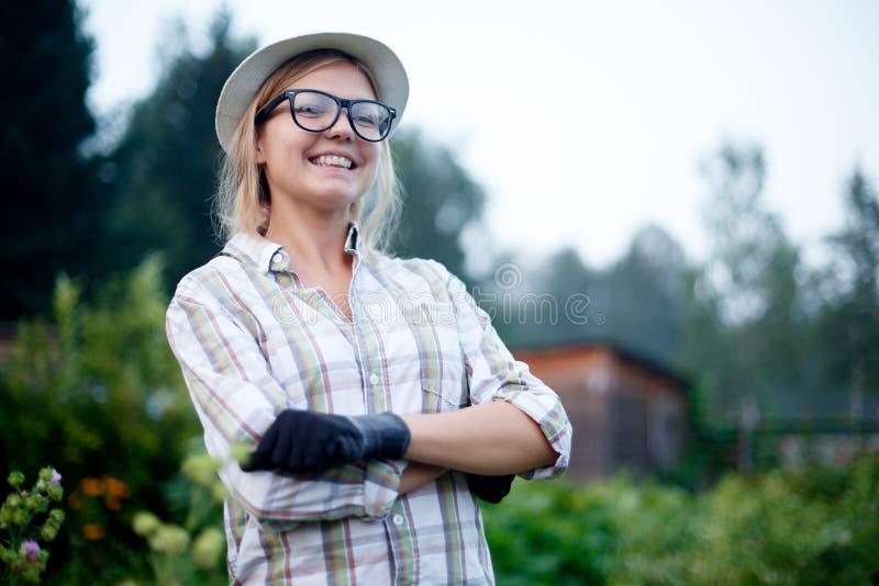 Retrato del jardinero sonriente feliz de la mujer joven con los guantes imagen de archivo