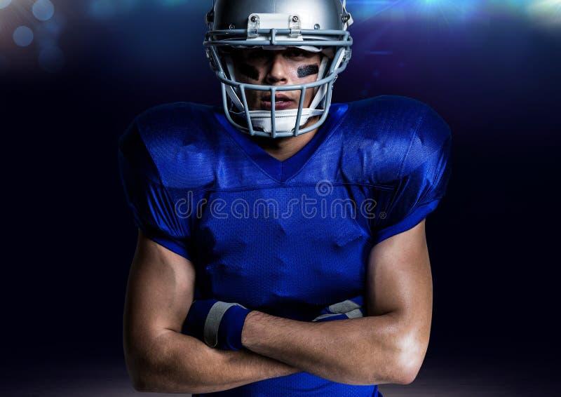 Retrato del jugador americano en el casco que se coloca con los brazos cruzados foto de archivo