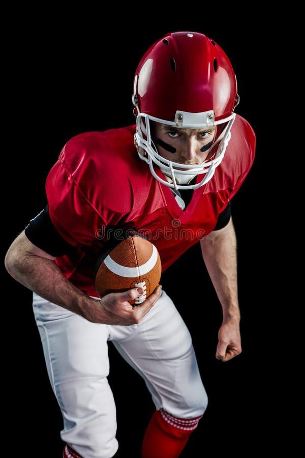 Retrato del jugador de fútbol americano enfocado que está listo para atacar fotografía de archivo