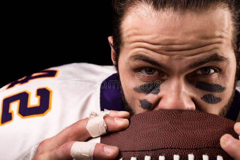 Retrato del jugador de fútbol americano que celebra una bola y que mira la cámara fotos de archivo