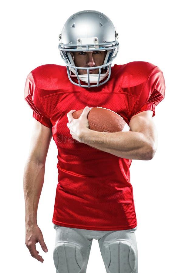 Retrato del jugador de fútbol americano serio en el jersey rojo que sostiene la bola imagenes de archivo