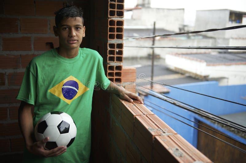 Retrato del jugador de fútbol brasileño joven que se coloca con fútbol imagen de archivo
