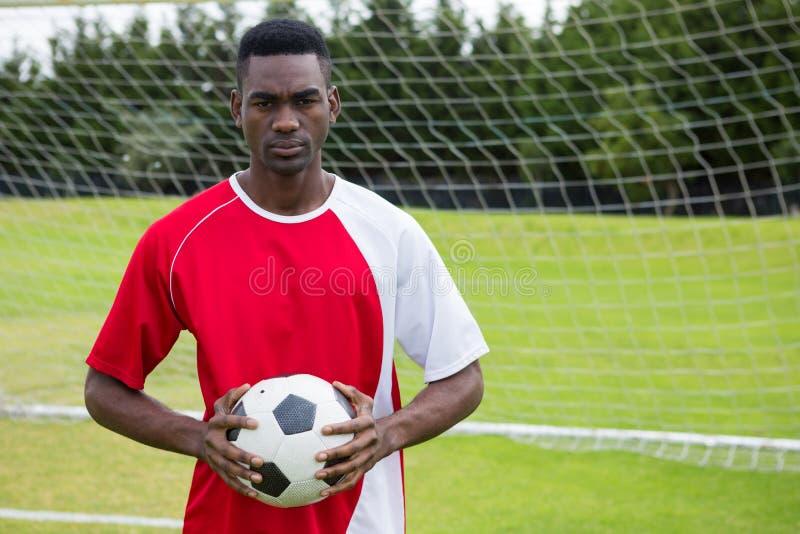 Retrato del jugador de fútbol de sexo masculino confiado serio que celebra la bola imagen de archivo libre de regalías