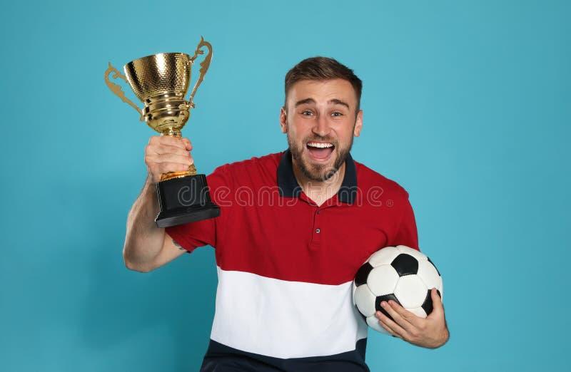 Retrato del jugador de fútbol joven feliz con la taza y la bola del trofeo del oro imagen de archivo libre de regalías