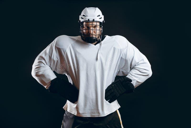 Retrato del jugador del hielo-hockey con el palillo de hockey foto de archivo