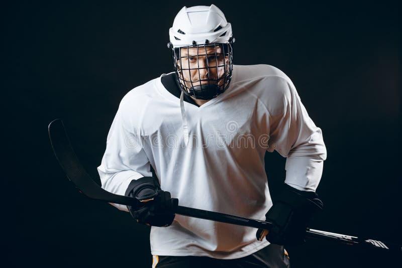 Retrato del jugador del hielo-hockey con el palillo de hockey y del duende malicioso aislado sobre negro imágenes de archivo libres de regalías