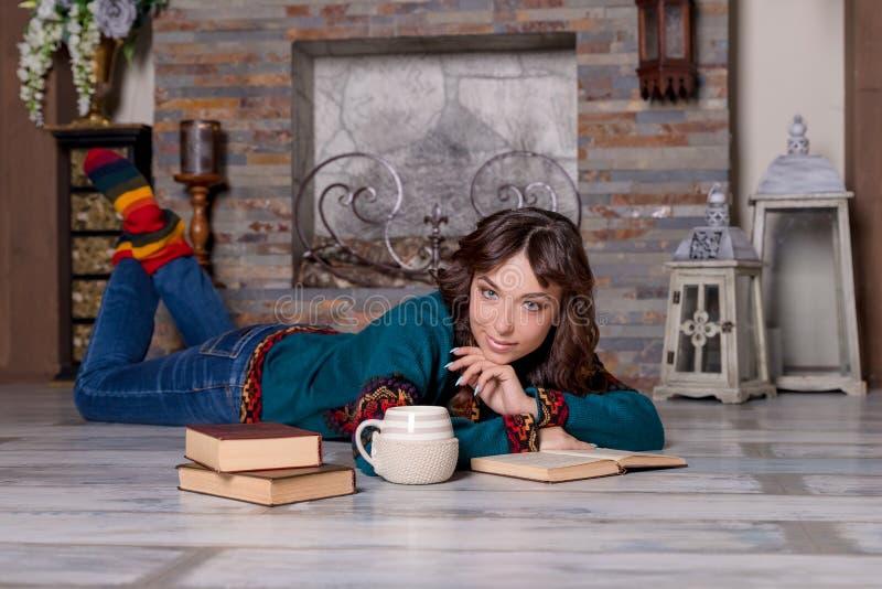 Retrato del libro de lectura moreno elegante georgeous de la mujer cerca de la chimenea acogedora Lanzamiento interior Lectura de foto de archivo