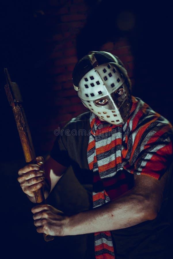 Retrato del maniaco con el hacha en el sótano oscuro imagen de archivo libre de regalías