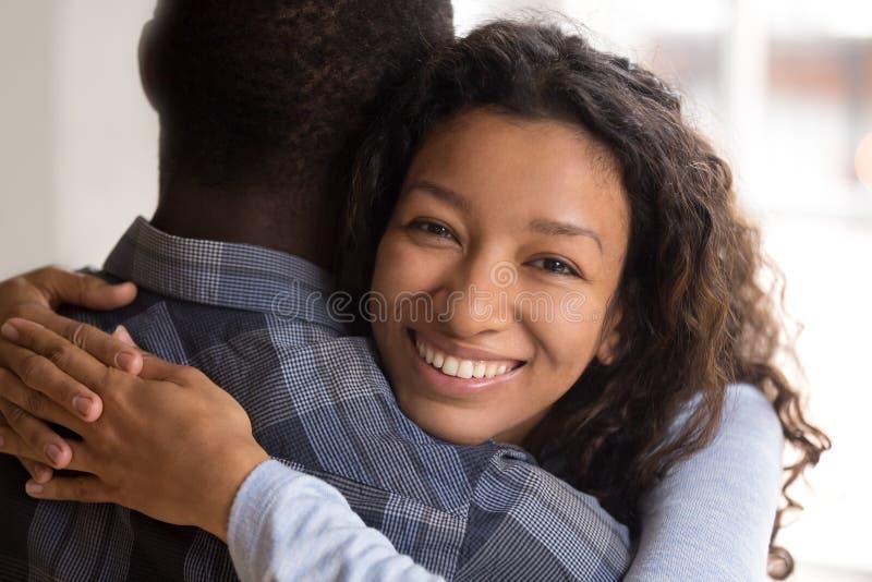 Retrato del marido de abarcamiento sonriente negro joven de la esposa fotos de archivo