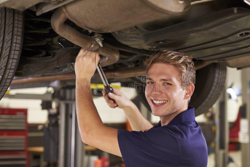 Retrato del mecánico de automóviles Working Underneath Car en garaje imagenes de archivo