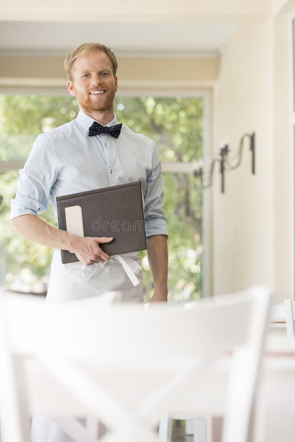 Retrato del menú joven confiado de la tenencia del camarero mientras que se coloca en el restaurante foto de archivo libre de regalías