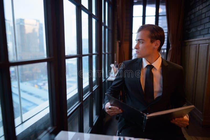 Retrato del menú joven de la tenencia del hombre de negocios y de la mirada fuera de ventana fotos de archivo libres de regalías