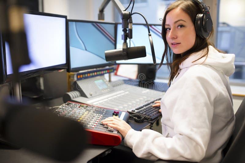 Retrato del micrófono de Using Headphones And del jinete en el estudio de radio fotografía de archivo