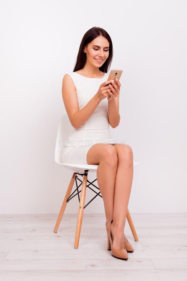 Retrato del mismo tamaño de la morenita linda que se sienta en la silla blanca y t foto de archivo