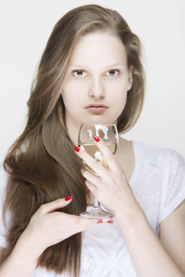 Retrato del modelo femenino joven que sostiene un vidrio de la bebida imagen de archivo