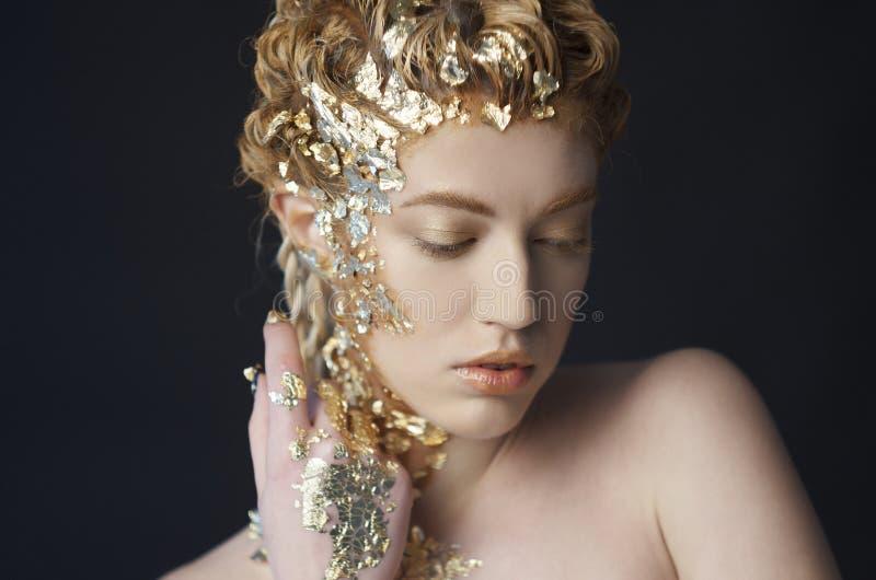 Retrato del modelo hermoso con la hoja brillante en cara y el pelo fotografía de archivo
