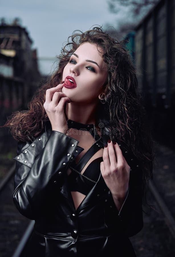 Retrato del modelo informal de la mujer atractiva del empeine vestido en la capa de cuero fotos de archivo