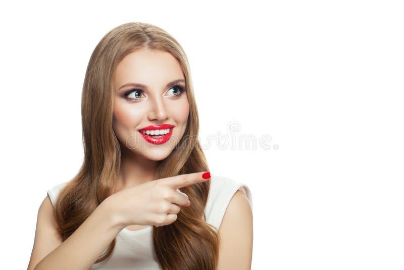 Retrato del modelo lindo hermoso joven de la mujer que señala a un lado aislado en el fondo blanco fotografía de archivo libre de regalías