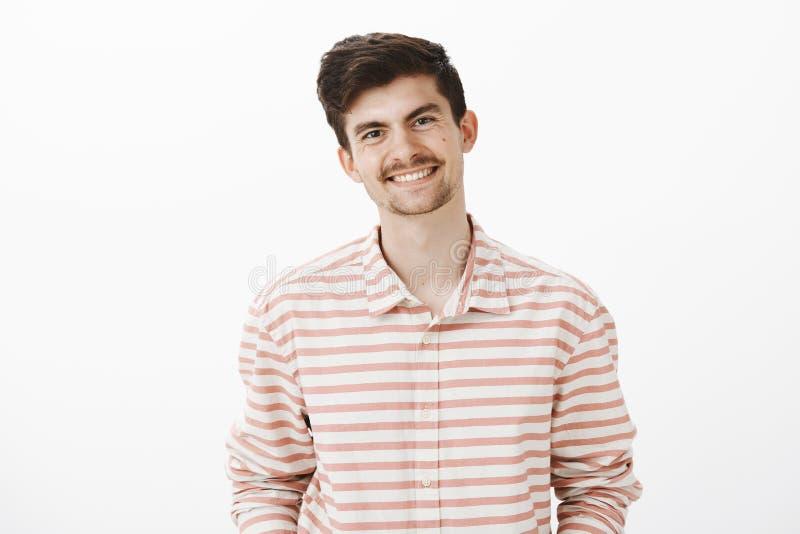 Retrato del modelo masculino amistoso apuesto con la barba y el bigote, sonriendo ampliamente mientras que habla con el compañero fotos de archivo libres de regalías
