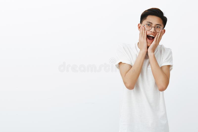 Retrato del modelo masculino asiático atractivo joven sorprendido y carismático emocionado con el peinado elegante en vidrios red imagen de archivo