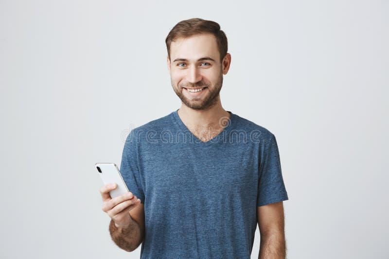 Retrato del modelo masculino europeo barbudo que mira feliz la cámara, expresando las emociones positivas, sosteniendo smartphone imagenes de archivo