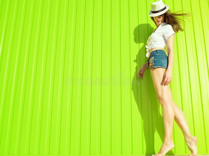 Retrato del modelo zanquilargo delgado magnífico con el pelo que agita largo Panamá blanca que lleva, la blusa y pantalones corto imagen de archivo libre de regalías