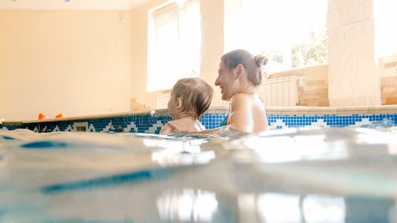 Retrato del mothet joven alegre feliz con 3 a?os del ni?o peque?o que juega en la piscina en la casa Aprendizaje del ni?o imagenes de archivo