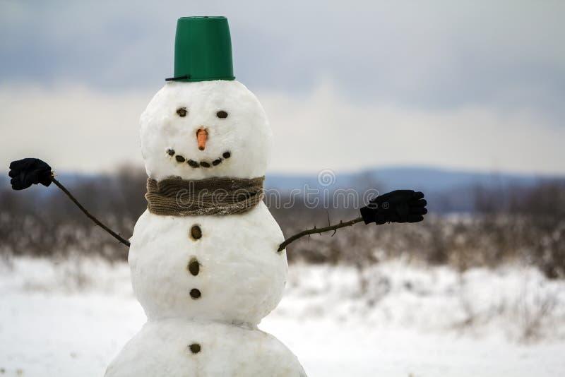 Retrato del muñeco de nieve feliz blanco con la nariz anaranjada de la zanahoria, piedras negras para los ojos y cubo verde en su foto de archivo