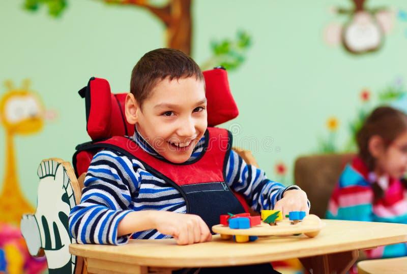 Retrato del muchacho alegre con incapacidad en el centro de rehabilitación para los niños con necesidades especiales fotos de archivo libres de regalías