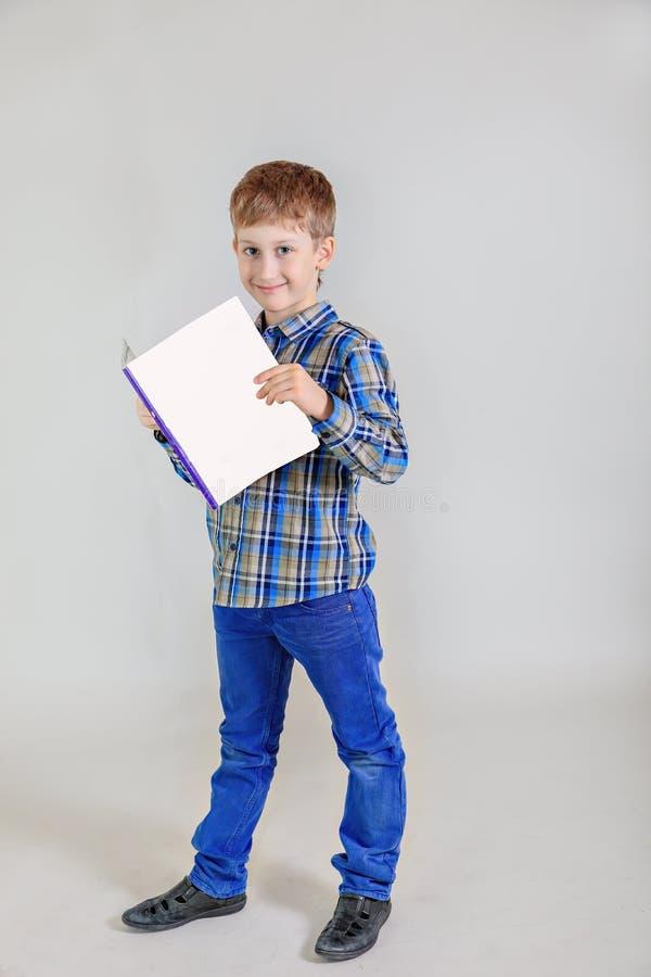 Retrato del muchacho aucasian del  lindo del pelirrojo Ñ, estudiante de la escuela primaria con el libro en fondo gris fotografía de archivo libre de regalías