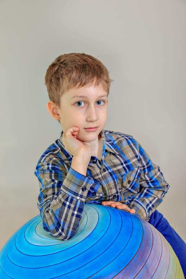 Retrato del muchacho aucasian del  lindo del pelirrojo Ñ, estudiante de la escuela primaria en fondo gris fotos de archivo
