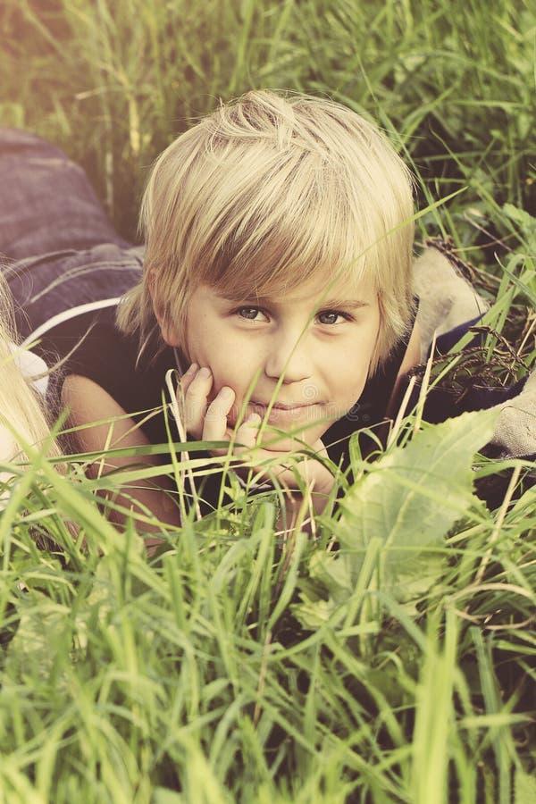Retrato del muchacho del niño en hierba al aire libre imagen de archivo