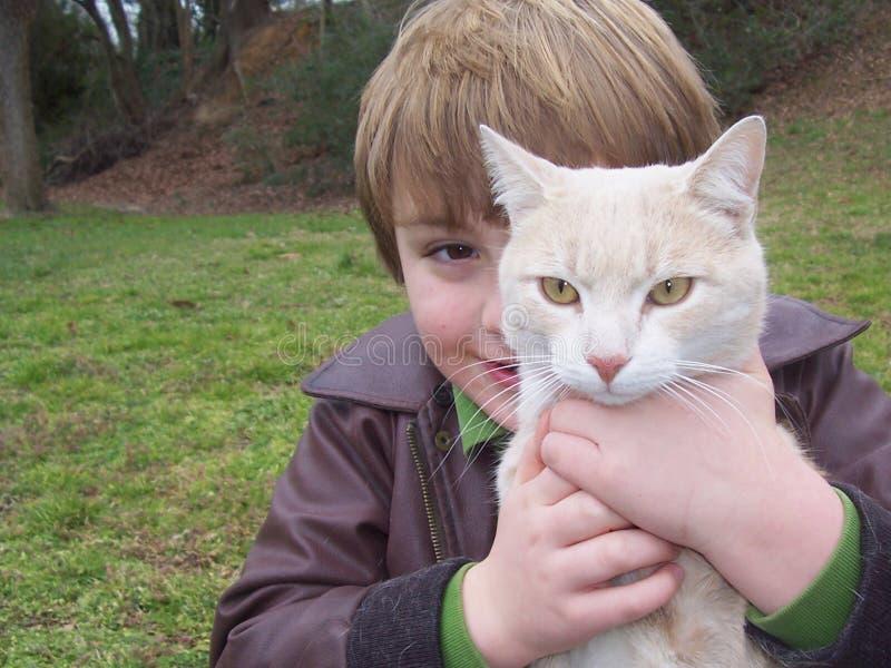 Retrato del muchacho detrás del gato foto de archivo libre de regalías