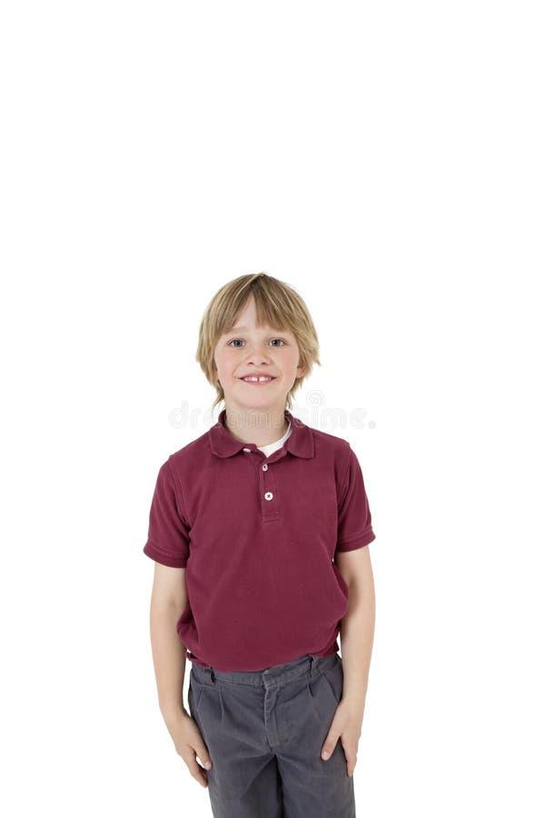Retrato del muchacho elemental feliz en uniforme escolar sobre el fondo blanco imagen de archivo
