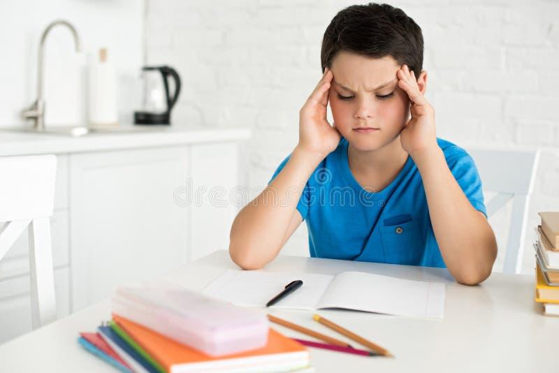 retrato del muchacho enfocado que se sienta en la tabla con la pluma y los cuadernos del cuaderno foto de archivo libre de regalías