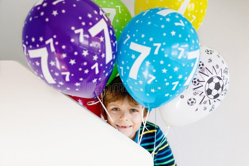 Retrato del muchacho feliz del niño con el manojo en los balones de aire coloridos en el cumpleaños 7 imagen de archivo