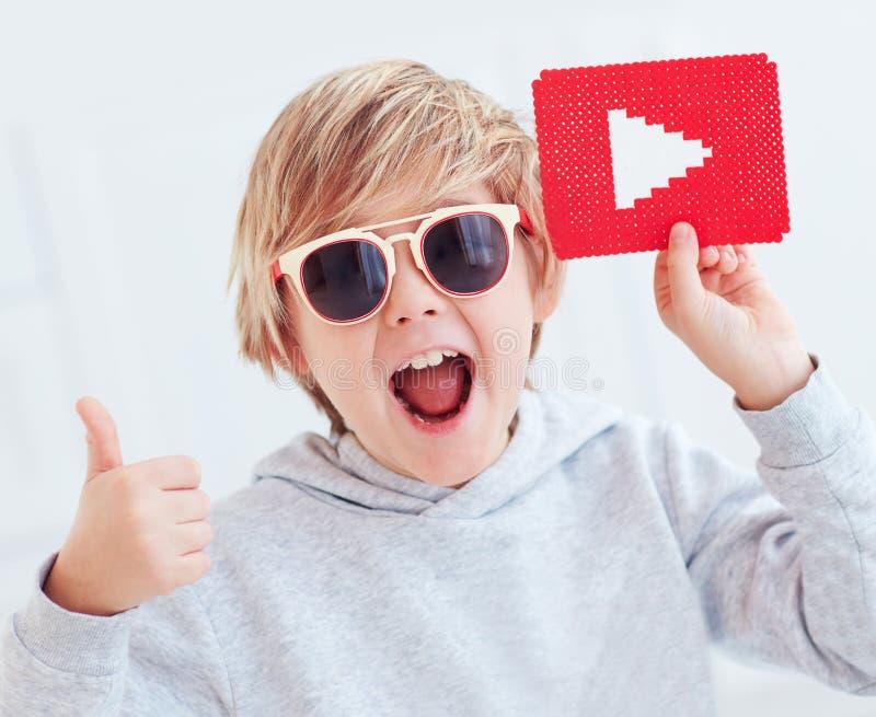 Retrato del muchacho feliz lindo, del niño con el icono del botón de reproducción y del pulgar para arriba foto de archivo libre de regalías