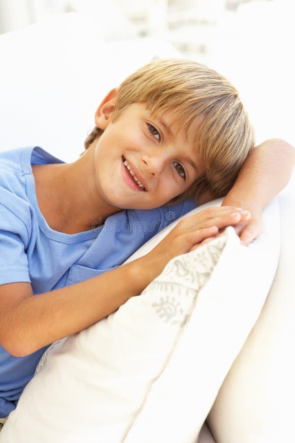 Retrato del muchacho joven que se relaja en el sofá foto de archivo