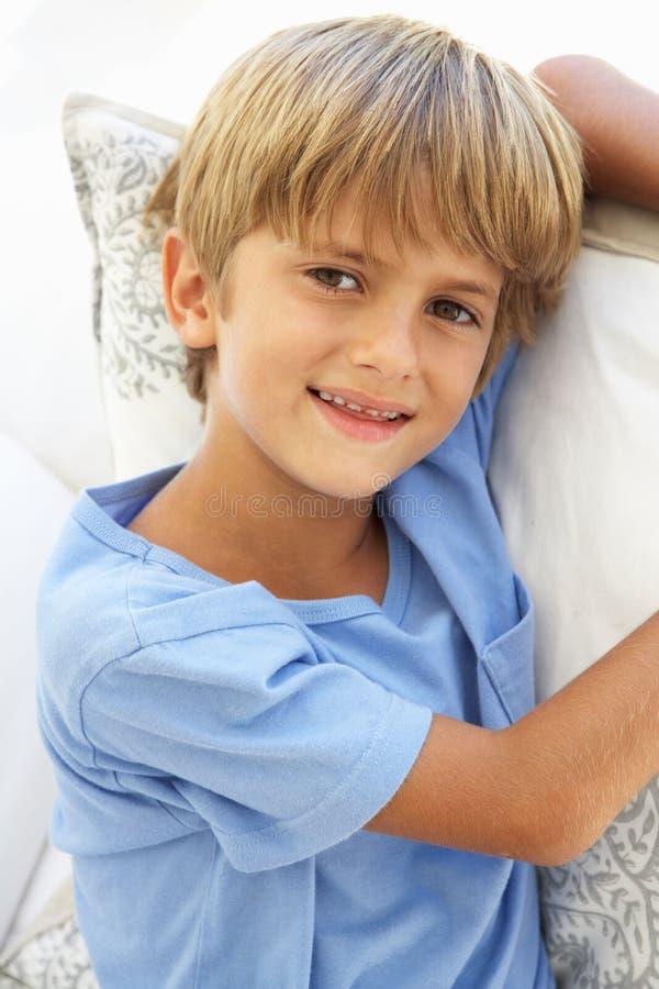 Retrato del muchacho joven que se relaja en el sofá imagen de archivo libre de regalías