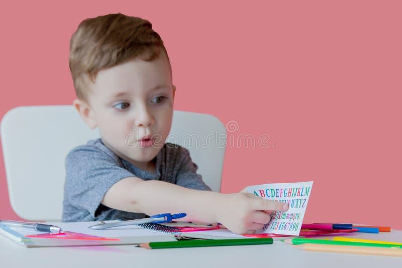 Retrato del muchacho lindo del niño en casa que hace la preparación Poco niño concentrado que escribe con el lápiz colorido, dent foto de archivo libre de regalías