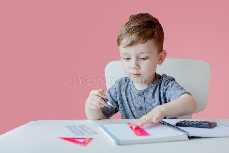 Retrato del muchacho lindo del niño en casa que hace la preparación Poco niño concentrado que escribe con el lápiz colorido, dent fotografía de archivo